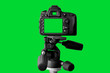 canvas print picture - The Dslr camera with green screen on the tripod isolated on green background. The chromakey. Green screen.