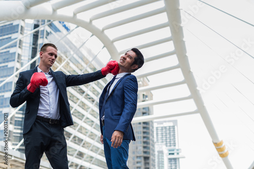 Photo  Caucasian man wear black suit and red boxing gloves punch to face of Asian man