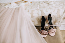 Pink Elegant Bride Shoes Next To A Beautiful Wedding Dress Lies On The Bed In A Hotel Room. Wedding Preparation