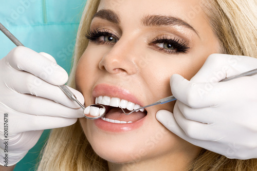 Photo Young beautiful woman with beautiful white teeth sitting on a dental chair