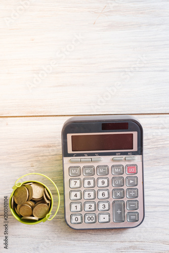 Fotografie, Obraz  Calculator with money and pennies on a wooden green background