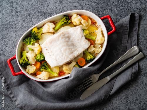 Zdjęcie XXL Rybi dorsz piec w piekarniku z warzywami - zdrowej diety zdrowy jedzenie. Siwieje kamiennego tło, zakończenie up, odgórny widok.