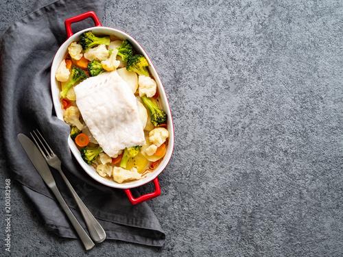 Zdjęcie XXL Rybi dorsz piec w piekarniku z warzywami - zdrowej diety zdrowy jedzenie. Szarości kamienny tło, kopii przestrzeń, odgórny widok.