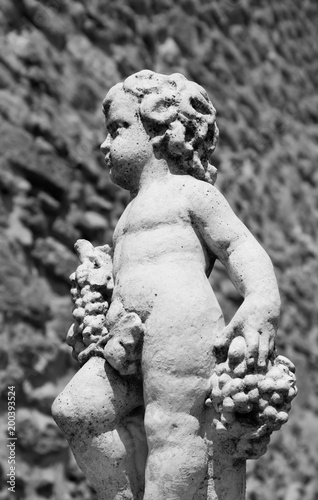 Photo Statue of Bacchus (Dionysus) with grapes in his hands against rough stone wall