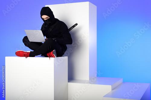 Photo ninja in black clothing using laptop while sitting on white block isolated on bl