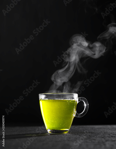 Stickers pour porte The Freshly brewed green tea in a transparent glass Cup,escaping steam,darker background.