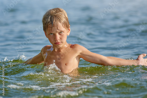 Portrait of young serious boy swimming in the lake at summer