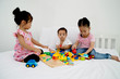 Three children playing toys in bed in the bedroom.