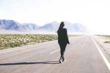 Young Woman With Long Hair Walks Alone On A Long Straight Road