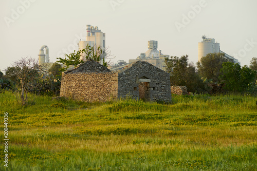 Valokuva  Sunset with old country house and big industry on the background in Salento- Ita