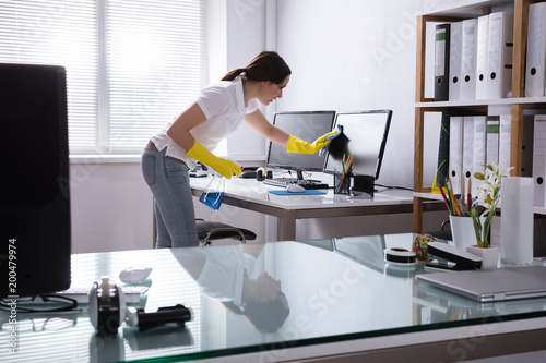 Woman Cleaning Computer In Office Canvas