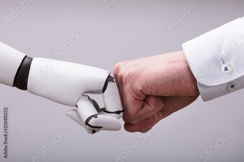 Foto  Robot And Human Hand Making Fist Bump
