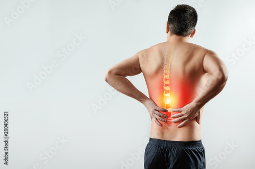 Fotografie, Obraz  Rear view, the man holds his hands behind his back, pain in the back, pain in the spine, highlighted in red
