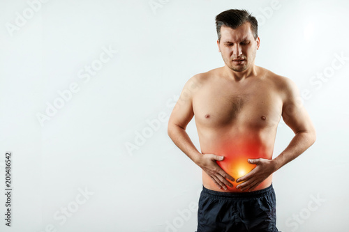 Fotografie, Obraz  Front view, the man holds his hands to the stomach, abdominal pain, pain in the stomach highlighted in red