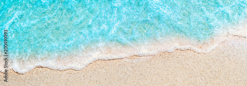 Stickers pour portes Eau Soft wave of blue ocean on sandy beach with copy space fr text. Summer Background.