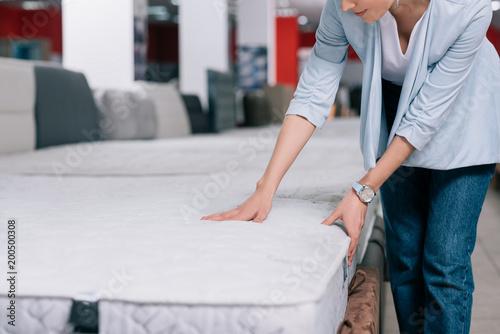 Fotografia  partial view of woman touching orthopedic mattress in furniture shop