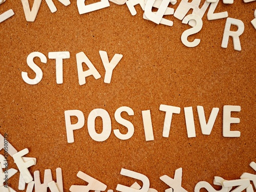"""Photo  """"Stay positive"""" writing with wooden letter on wood board, top view"""