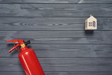 Residence Fire Safety. Top View Of Red Fire Extinguisher And Small House On Wooden Planks