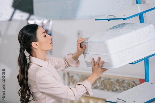 Fotografia  side view of female customer choosing orthopedic folding mattress in furniture s