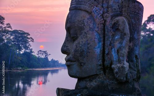Stone statue on causeway near Gate of Angkor Thom in Siem Reap, Cambodia. Angkor Thom is a popular tourist attraction.