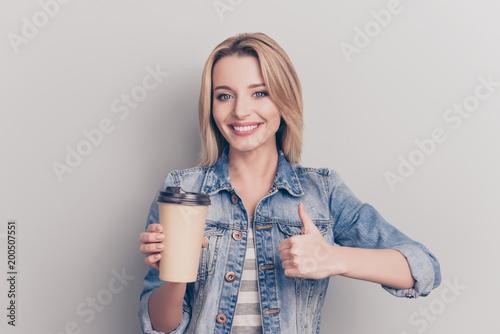 Fototapeta Portrait of pretty, lovely, sweet, modern, stylish girl having mug of tea in hand, gesture thumb up symbol, wearing jeans shirt, looking at camera, isolated on grey background obraz na płótnie