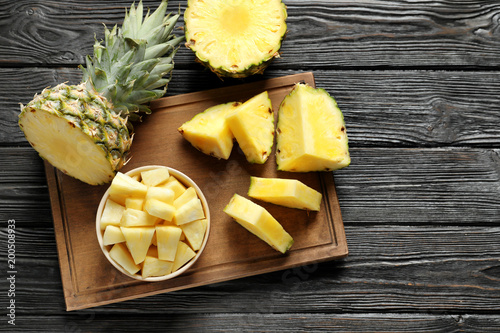 Wooden board with fresh sliced pineapple on table, top view
