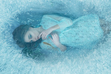 A Mermaid Girl In A Blue Vintage Dress Lies At The Bottom Of The Lake. It Is Covered With Ice Edge, Fish Swim Around It. She Mysteriously Looks Through The Ice With Her Finger Against Her Lips