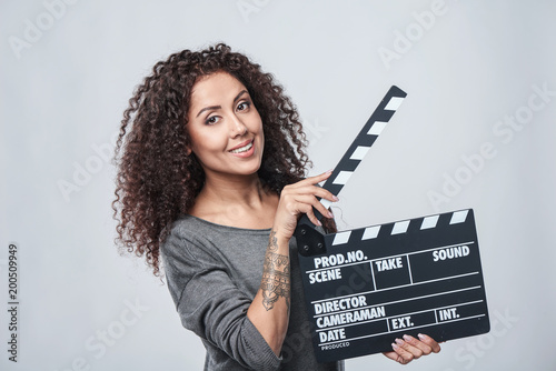 Smiling curly female holding movie clapper board, slate film. Canvas Print