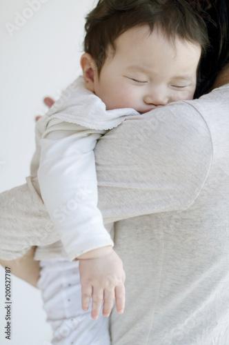 母親に抱かれ眠る赤ちゃん