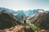 Woman traveler raised arms standing alone on cliff in mountains landscape Travel healthy Lifestyle adventure active vacations getaway in Norway