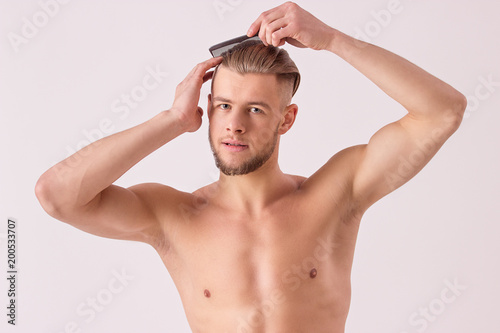 26c4cea24d Studio shot of attractive young man combing his hair with hairbrush while  standing shirtless and isolated