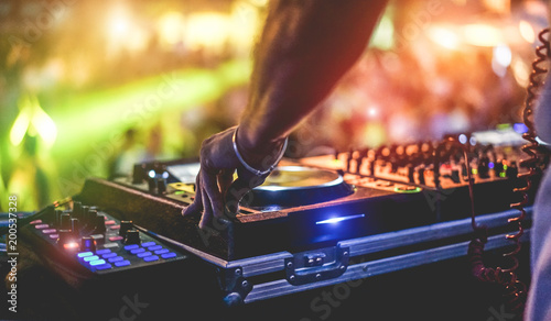 Dj mixing outdoor at beach party festival with crowd of people in background