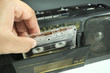 insert an audio cassette into a tape recorder