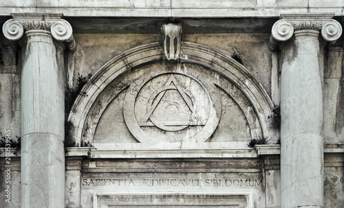 Eye of Providence, inside triangle interlaced with circle above doorway of building in Venice, Italy - It represents the eye of God watching over humanity, or divine providence Fototapeta