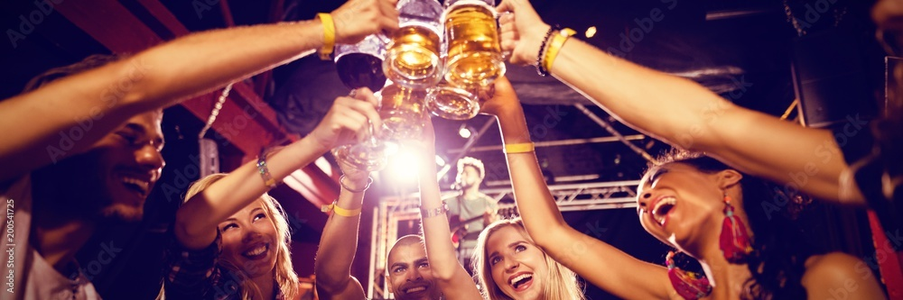 Fototapety, obrazy: Friends toasting beer glasses at table in club