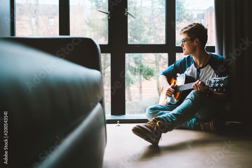 Fotografie, Obraz  Boy with guitar sits on the floor at cozy home, moody day light