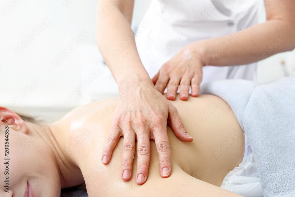 Fototapeta Masaż.  Masażysta masuje plecy w salonie spa.