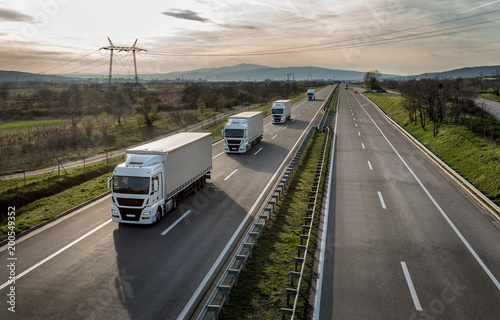 Caravan or convoy of trucks in line on a country highway Canvas