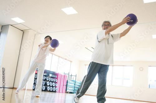 スポーツジムで運動するシニア夫婦
