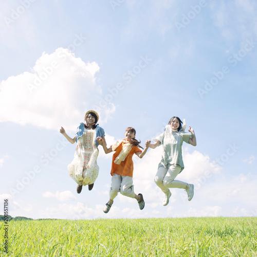 草原でジャンプをする3人の女性