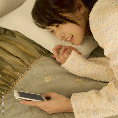 ベッドに寝転びスマートフォンを操作する女性