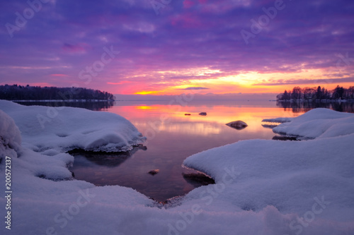 Poster Prune winter image of a lake at sunset with snow and stones in the foreground