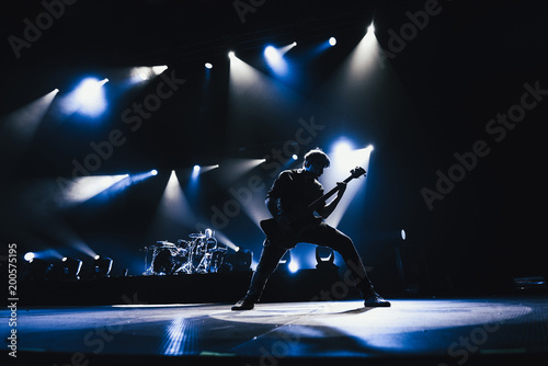 Rock band performs on stage. Guitarist plays solo. silhouette of guitar player in action on stage in front of concert crowd.