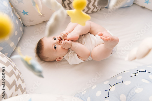Cute baby lies in a white round bed Wallpaper Mural