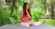 Young Latina woman with serene expression meditating with prayer beads outdoors