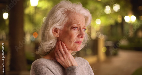 Fotografie, Obraz  Close view of mature white woman with unhappy look on face outside at night
