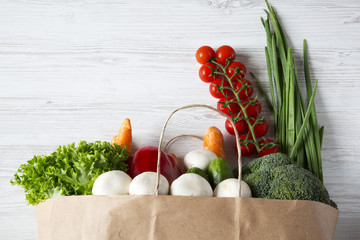 Paper bag of different vegetables on wooden background. Healthy food. Top view. From above. Copy space.