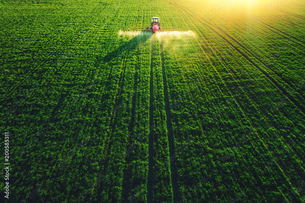 Fototapety, obrazy: Aerial view of farming tractor plowing and spraying on field