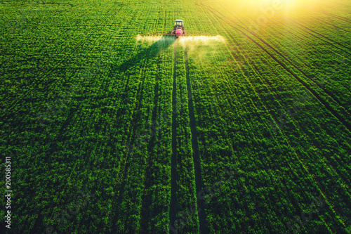 Fotografering Aerial view of farming tractor plowing and spraying on field