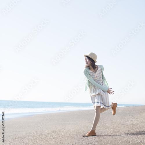 海に向かって貝殻を投げる女性
